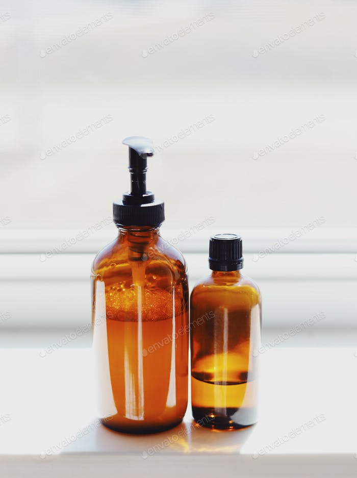 Minimal view of amber glass bottles with cleaning supplies