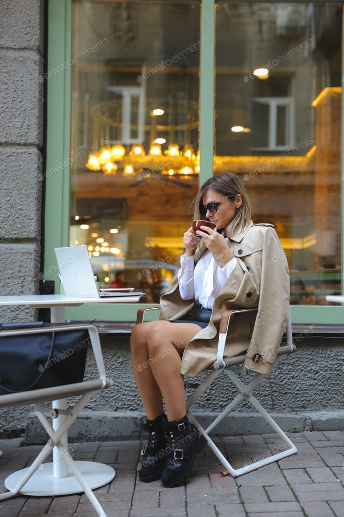 beautiful girl in glasses,a trench coat dressed in a casual style,working on a laptop and drink coff