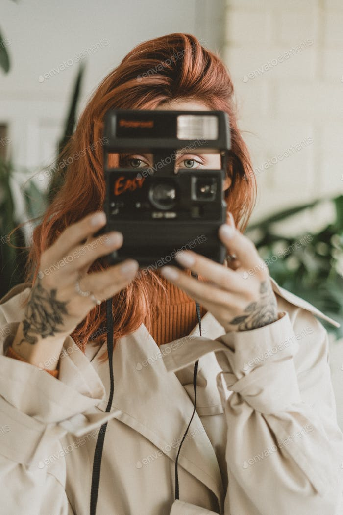 Girl holding retro Polaroid camera in her hands. Portrait shot with red hair woman
