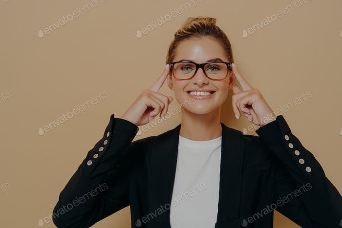 Positive blonde female student putting on eyeglasses and holding them with hands