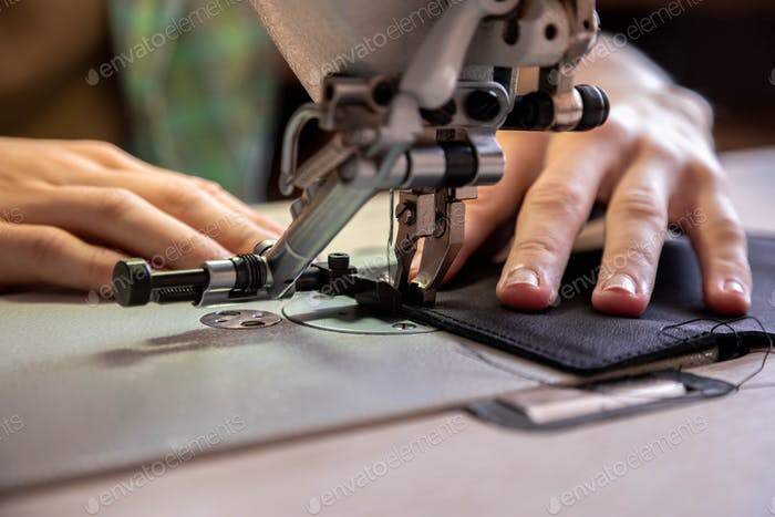 Close up craftsman hands sew stuff blank for wallet use sewing machine. Working at leather workshop