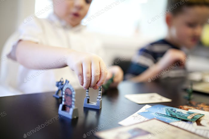 kids playing hero quest dice rolling adventure game like dungeons and dragons with dad