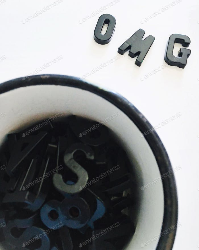 Looking down at a white enamel coffee mug with black rim holding letters of the alphabet and OMG