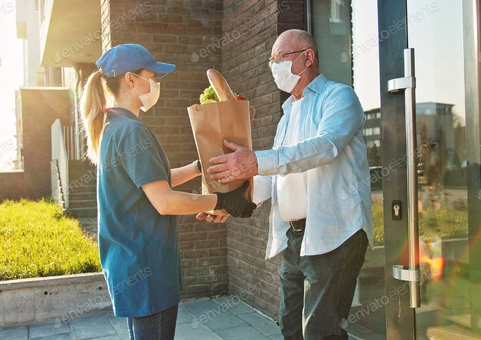 A young woman courier wearing a medical mask and protective gloves delivers a food bag. Working in a