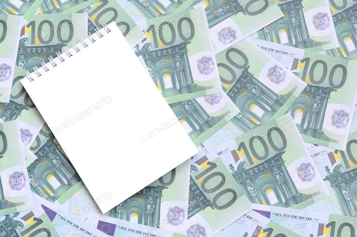 Cuaderno blanco con páginas limpias en un conjunto de denominaciones monetarias verdes de 100 euros