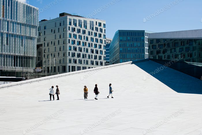 Five tourists walking on the roof of Opera House in Oslo, modern architecture, people, minimalism