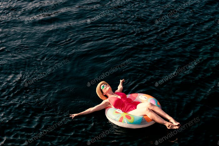 Woman red bathing suit on inner tube