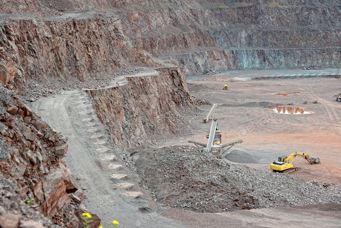 Stone crusher and excavator in a porphyry quarry. mining industry