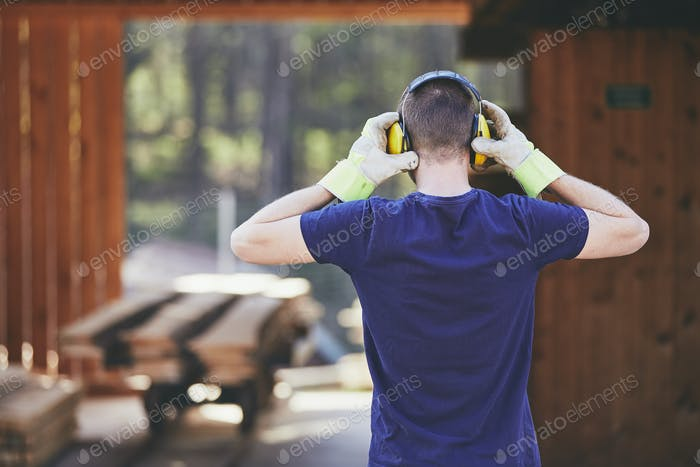 Man working in sawmill. Rear view of the worker with headset.
