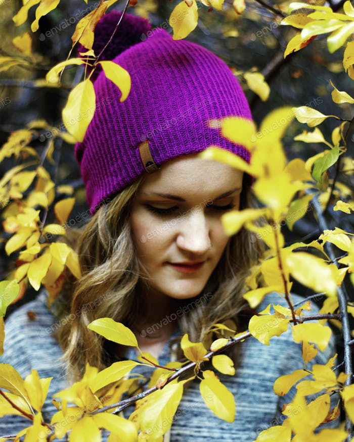 Girl with magenta beanie in fall foliage