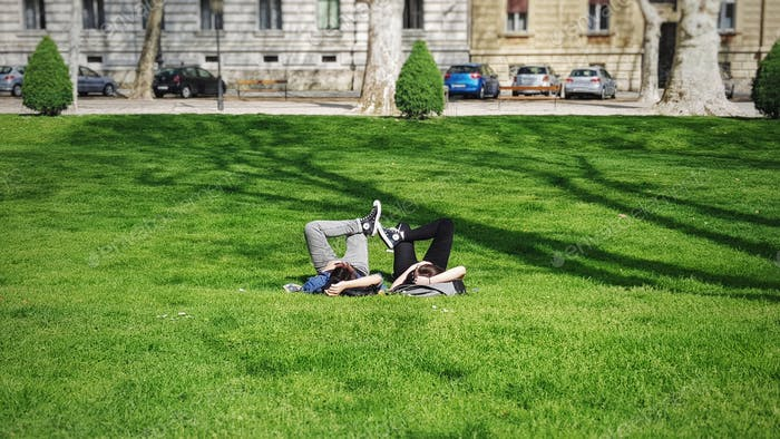 A young millenial couple laying on grass and relaxing