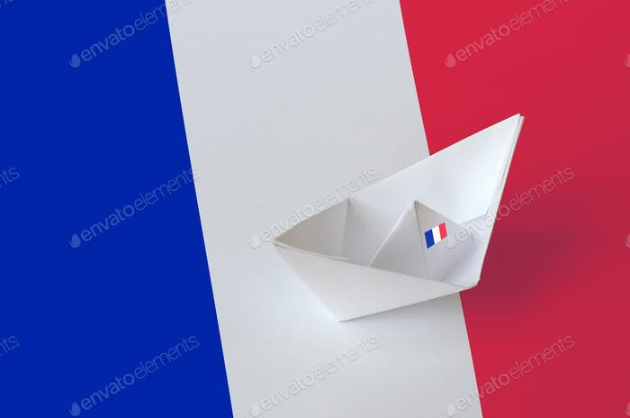 France flag depicted on paper origami ship closeup. Oriental handmade arts concept