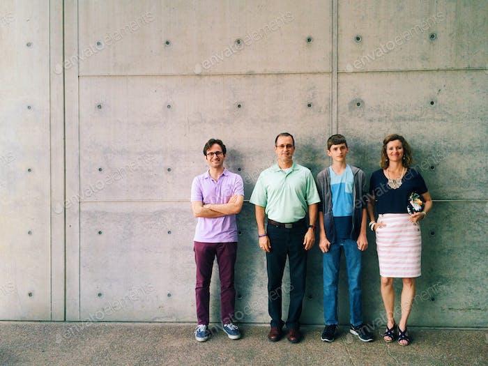 Uma família de quatro poses em frente a um muro urbano moderno.