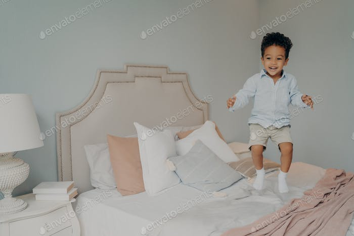 Happy carefree mixed race ethnicity kid boy in casual clothes having fun and jumping on bed