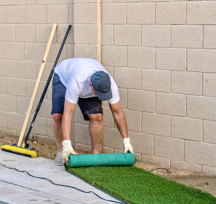 Adult male unrolling artificial grass or synthetic turf for installation in a small backyard space