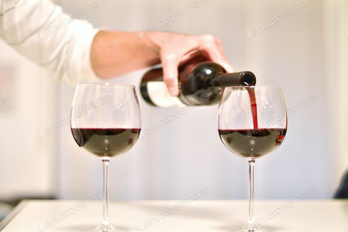 red wine is poured into crystal goblets