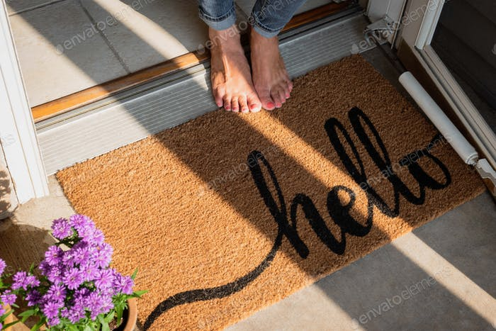 woman in bare feet standing by welcome mat in front of new home