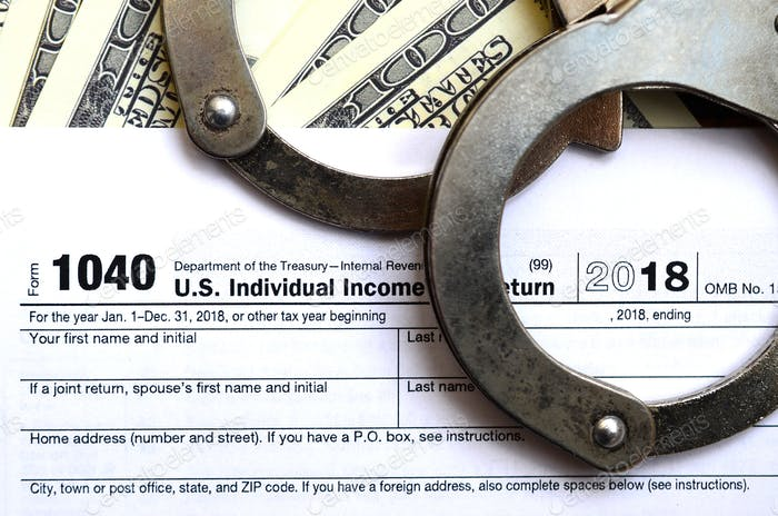 Police handcuffs lie on the tax form 1040