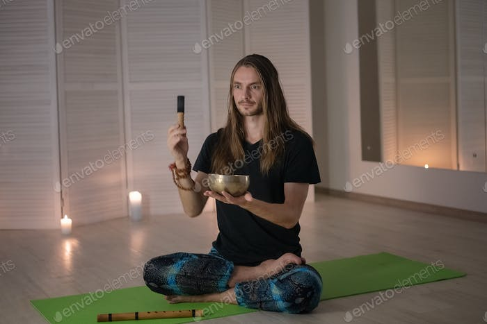 Ein junger männlicher Yogi meditiert friedlich und hält eine tibetische buddhistische Schüssel für Yoga und Meditation.