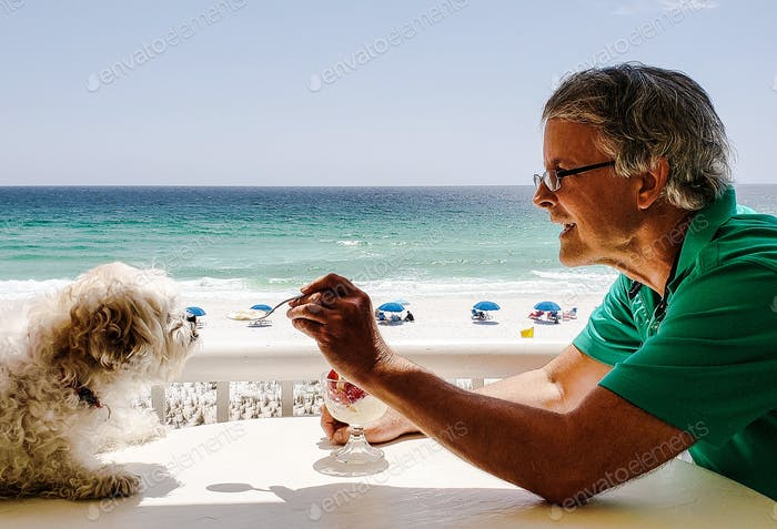 Active babyboomer sharing his icecream sundae with his sweet little doggie...