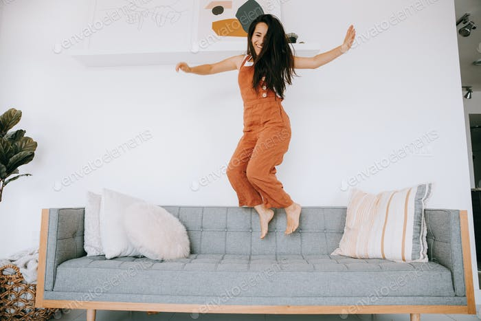 Young woman happy jumping on the couch