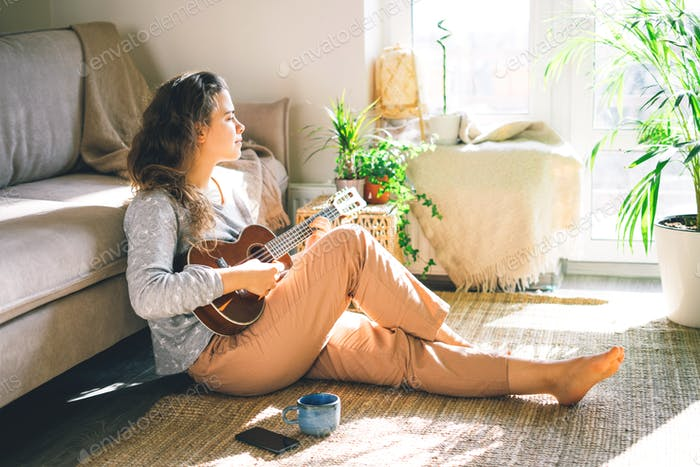 Young beautiful woman plays ukulele, sings and looking away