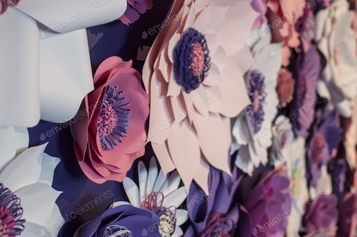 Un cierre de una pared escultura de flores en tonos de rosa, púrpura y blanco
