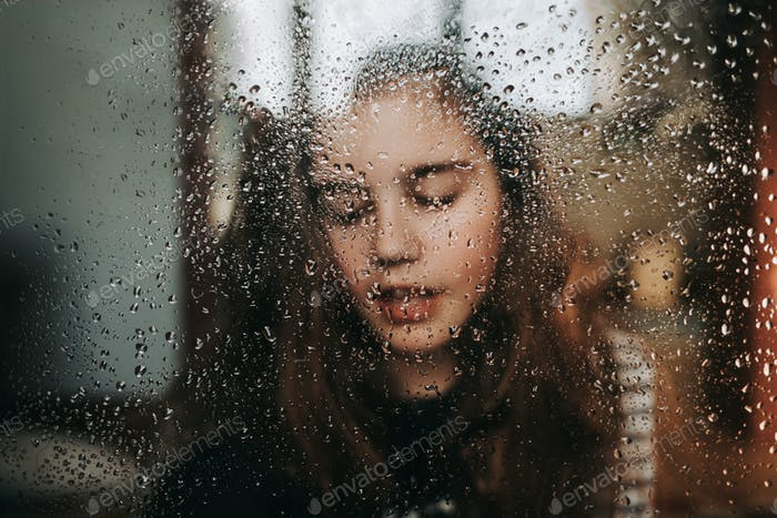 Preteen not looking at camera through the window with rain on it