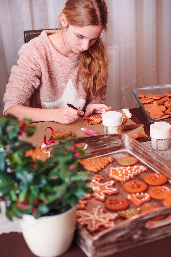 Teenager-Mädchen schmückt gebackene hausgemachte Lebkuchen Weihnachtsplätzchen mit Zuckerguss am