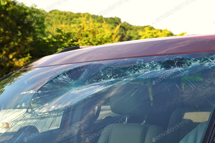 Damage to a vehicle windshield after an accident where it was hit by flying debris on the highway.