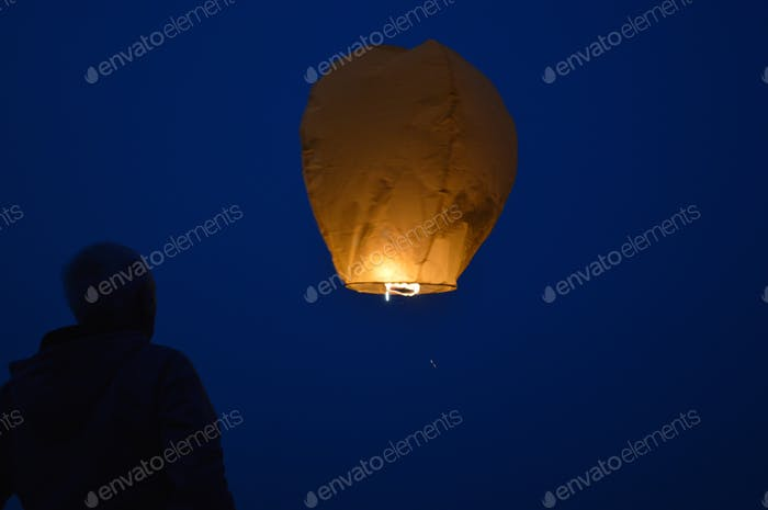 A man releasing a Kongming lantern in the night sky. Celebrations around the world.