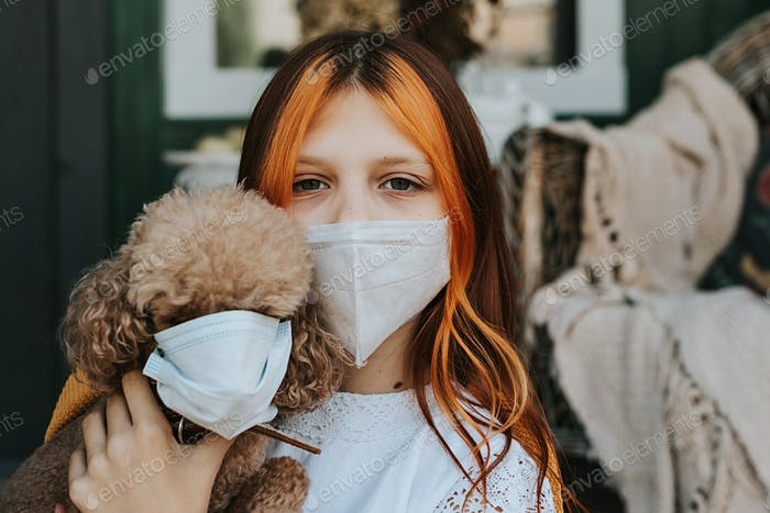 girl and her dog in protective masks on the porch of a house, the concept of the covid-19 pandemic
