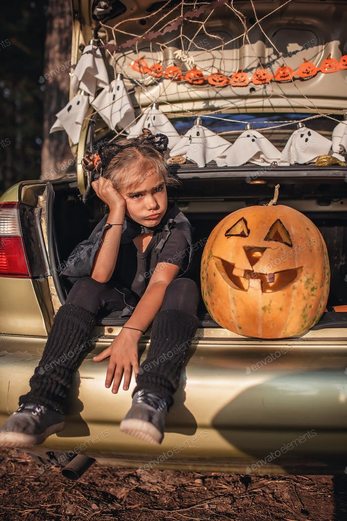 Alternative safe celebration. Girl in bat costume boring preparing Halloween party in trunk of car