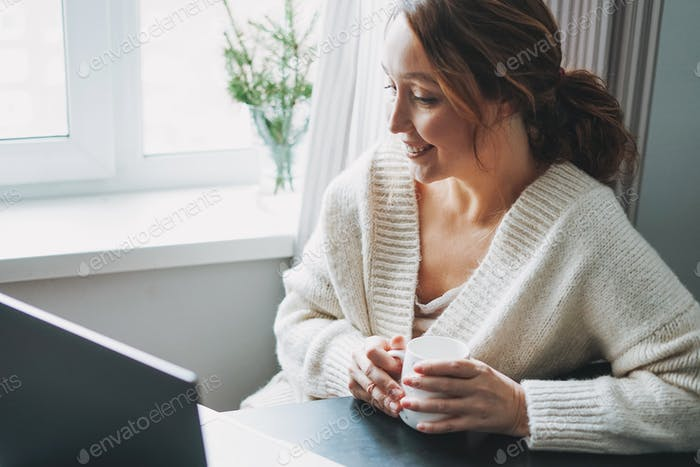 Attractive friendly smiling brunette woman middle age using laptop at home cozy vibes winter season