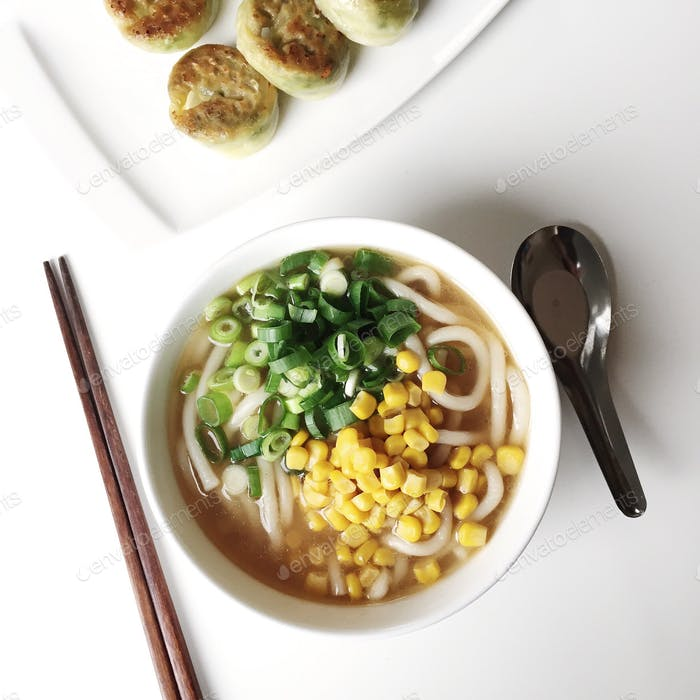 Bowl of udon noodles with corn an green onion, and a plate of Korean dumplings