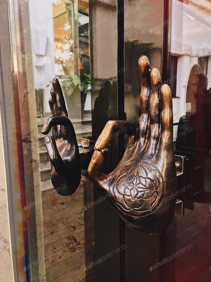 Om gyan mudra. Handles of glass door in yoga center