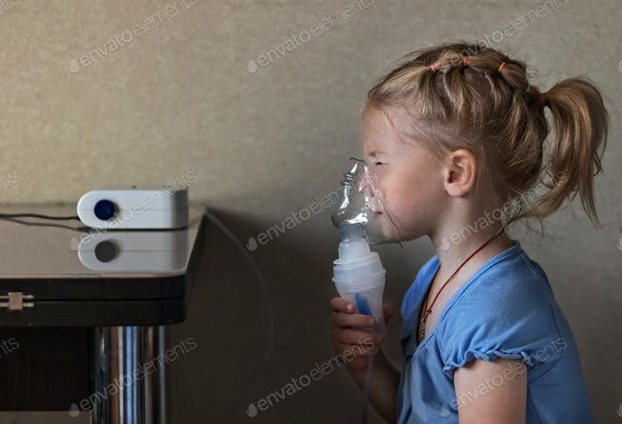 Little girl makes inhalation with a nebulizer at home, sitting on a chair.
