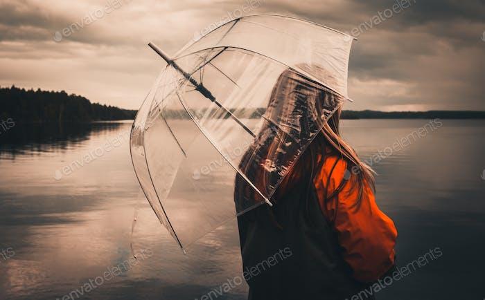 Wet weather. Lonely girl in grey-orange jacket hold umbrella. Raining on the lake. Wet umbrella agai