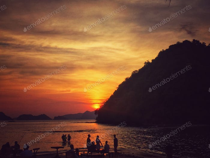 People happily drinking and enjoying the sunset by the beach in a secluded beach island