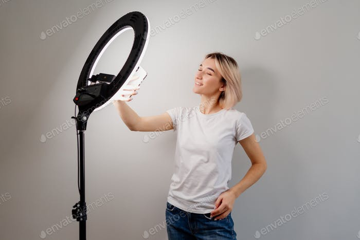 young girl blogger in a white t-shirt is broadcasting live on social networks using a ring lamp