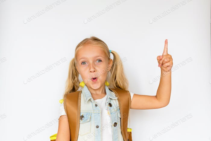 Smart school girl with backpack showing something interesting on white background