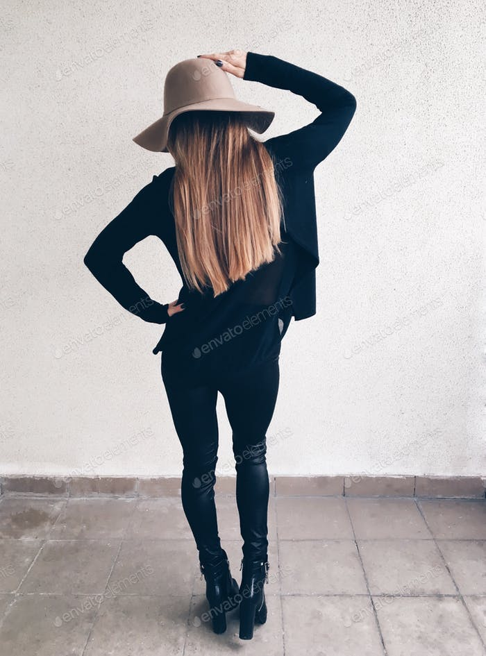A girl in the black leather leggings, cardigan and modern stylish hat is standing back near the wall