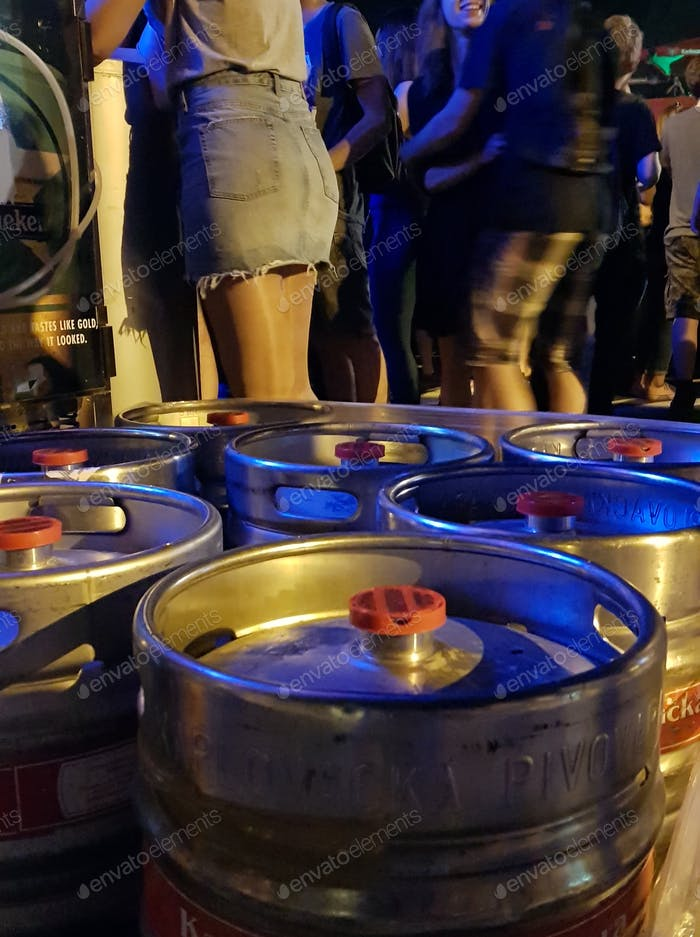 Close-up night shot of beer kegs at a music festival.