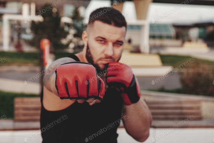 Sporty man athlete in boxing gloves, MMA fights strikes looking at camera against background of park