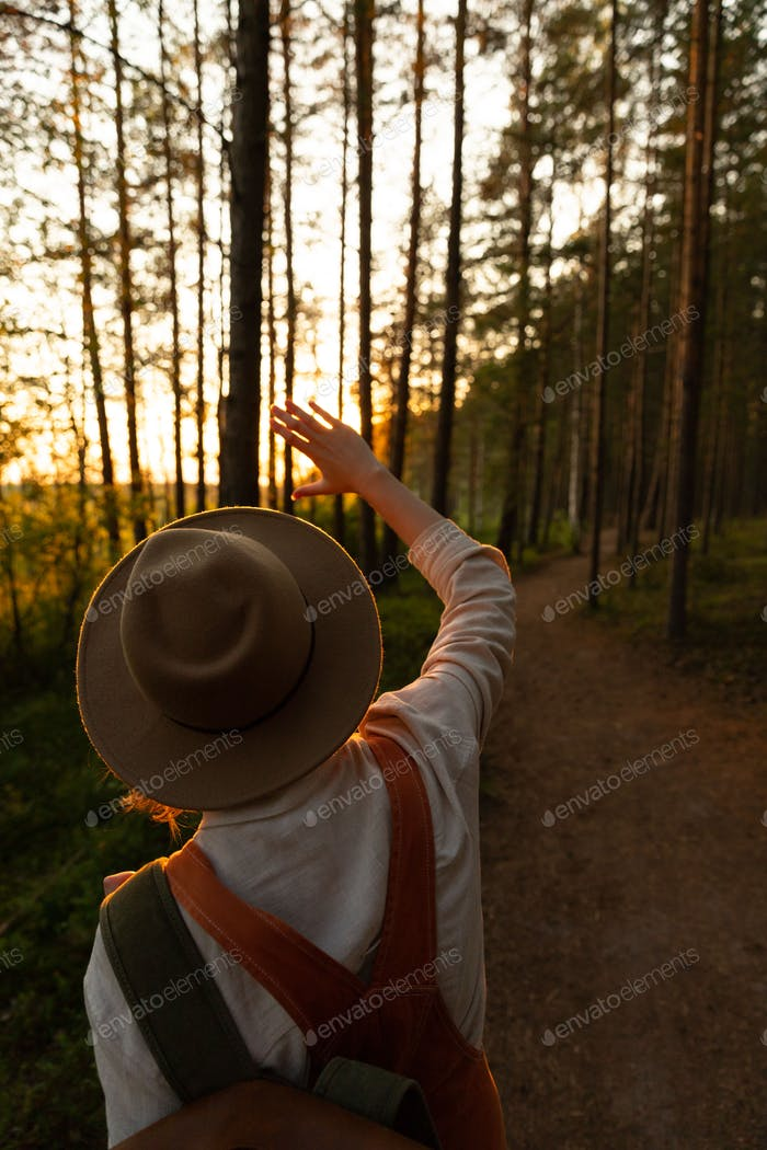 Woman naturalist in hat and overalls with backpack looking at the sun through her fingers at sunset
