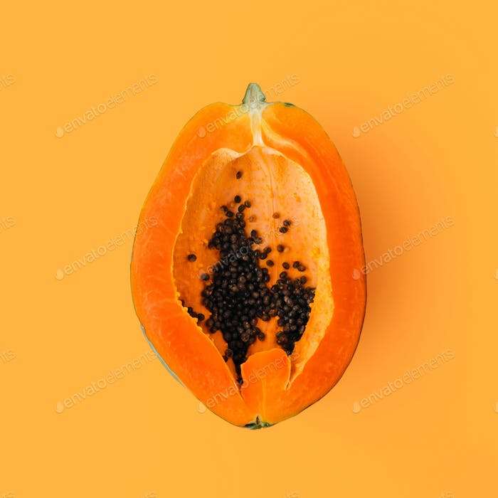 Papaya on an orange background with clipping path, creative food concept, tropical fruit flat lay