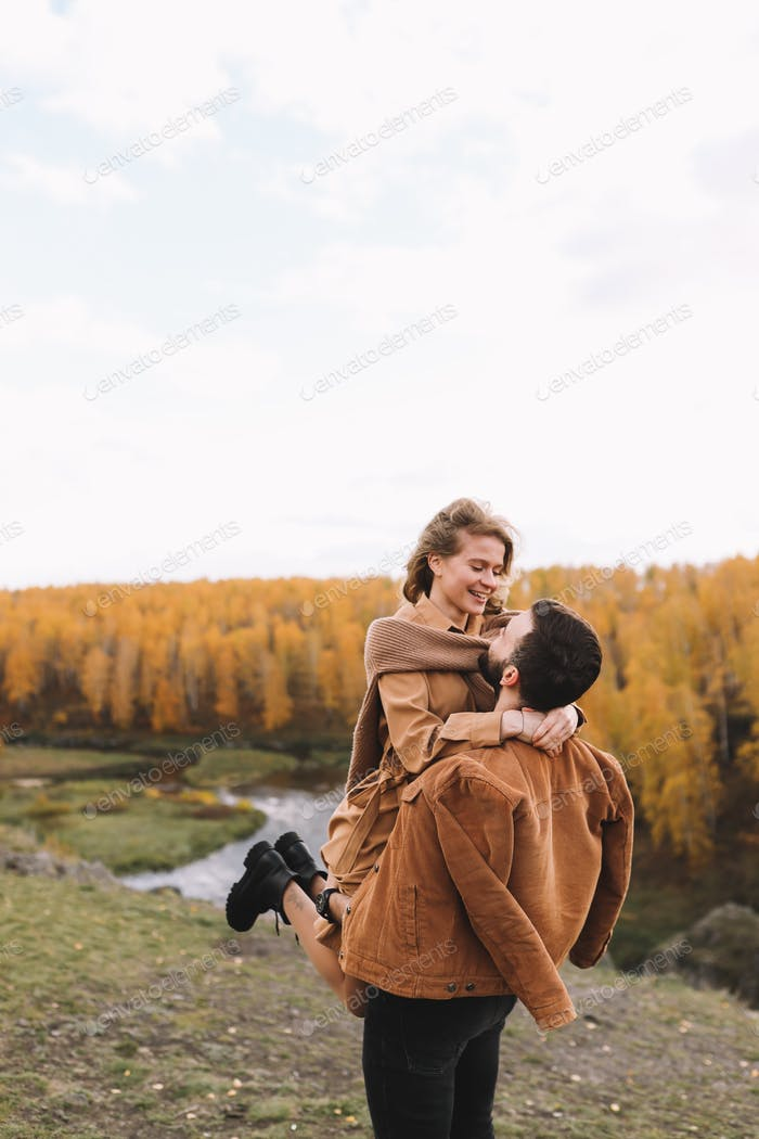 Happy people couple are traveling hiking in the autumn forest by the golden fall river outdoors
