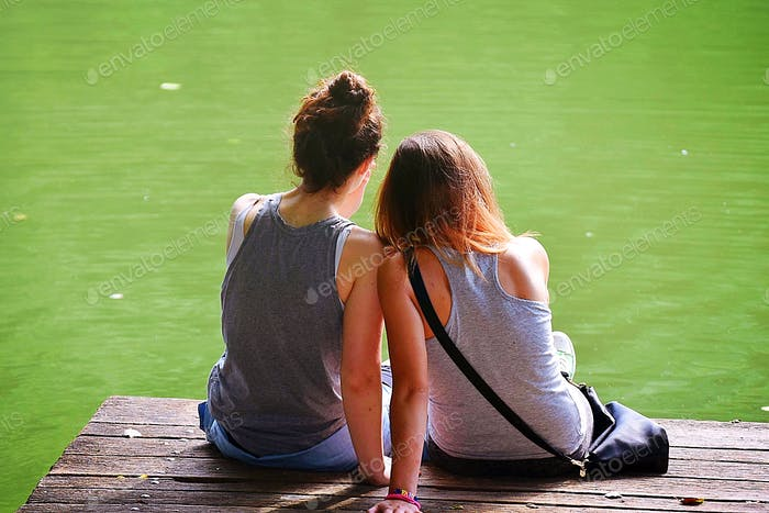 Two young girls sitting at the dock of a bay and admiring the green water. People from behind.