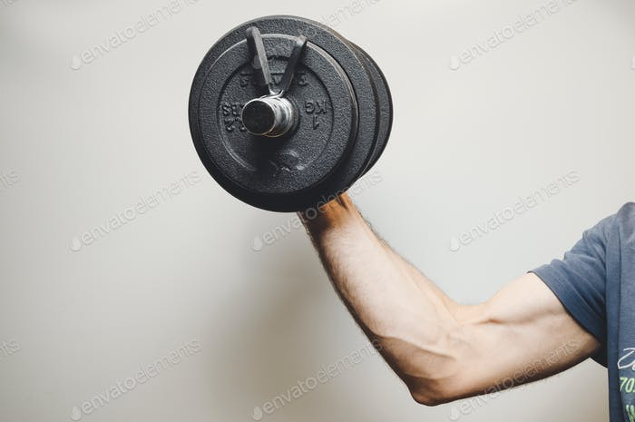 Man lifting weights at the gym with space for copy