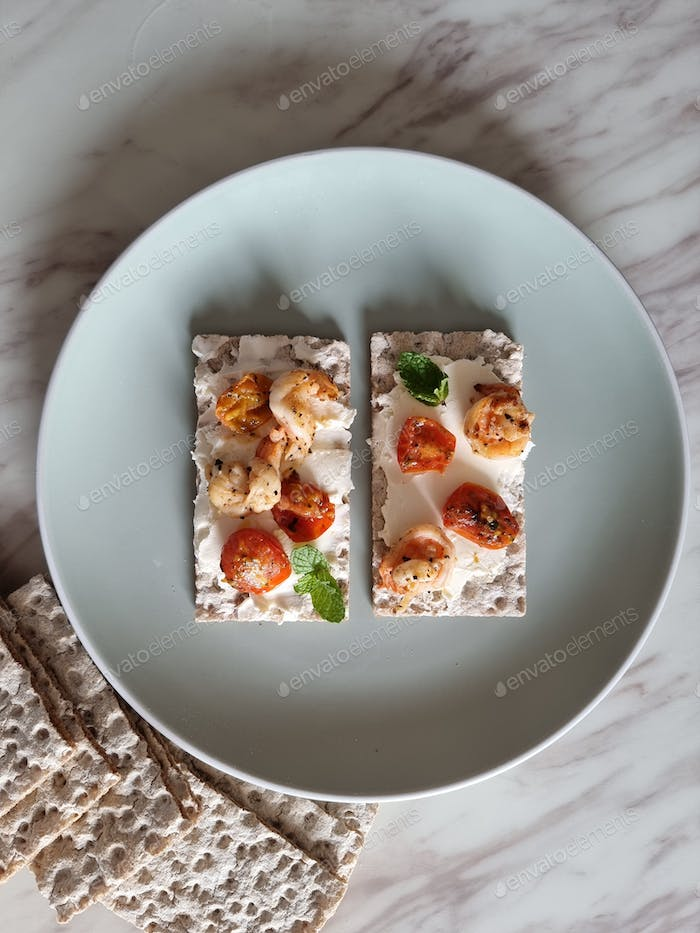 Whole grain crispbread with cream cheese, grilled cherry tomatoes, prawns and mint leaves